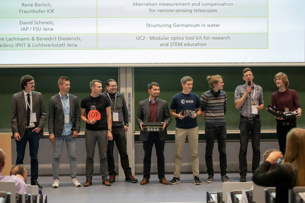 Participants in the elevator pitches on the stage of a lecture hall present their research ideas.
