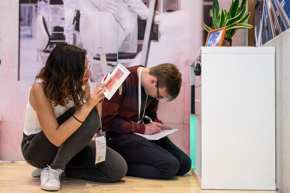 Zwei Studierende suchen auch mit Lupen nach Hinweisen, um wissenschaftliche Rätsel im Escape Room zu lösen.