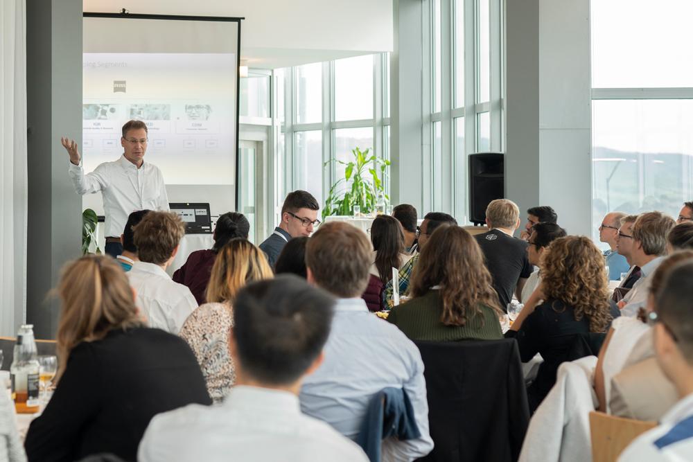 Firmenvertreter stellt sein Unternehmen den interessierten Studierenden und Promovierenden vor.