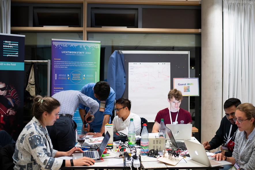 Teilnehmerinnen und Teilnehmer vor ihren Laptops und am gemeinsamen Schrauben.