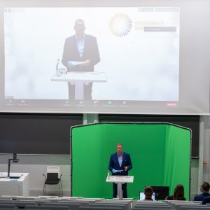 Prof. Andreas Tünnermann in front of a green screen in the lecture hall.