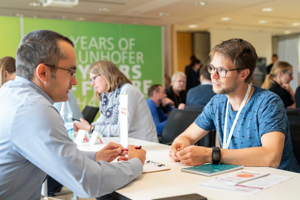 Zu zweit am Tisch sprechen Interessierte mit den Firmenvertreterinnen und -vertretern über einen Berufseinstieg in die Optik- und Photonik-Branche.