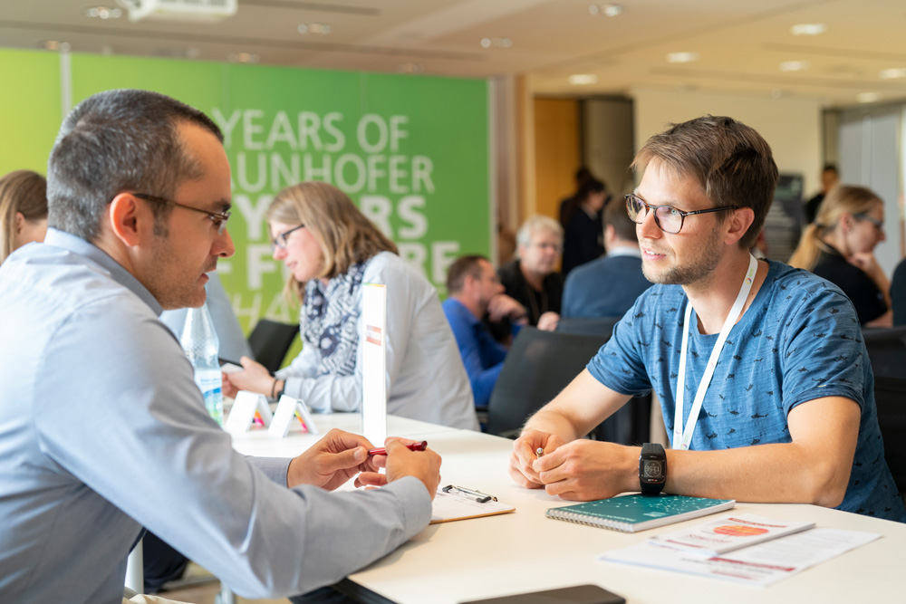 In pairs at the table, interested parties talk to company representatives about starting a career in the optics and photonics industry.