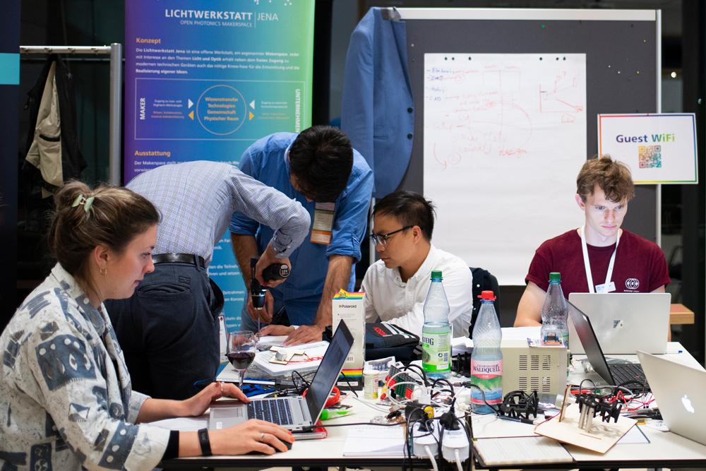 Studierende bauen Geräte zusammen und recherchieren am Laptop.